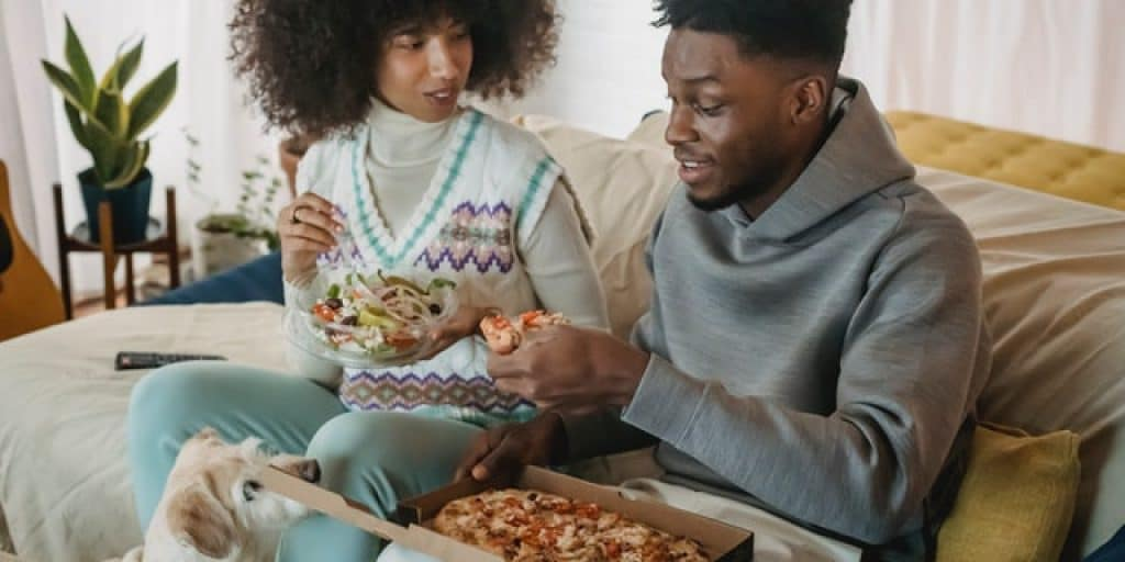 couple with a dog having pizza to avoid back pain when hungry