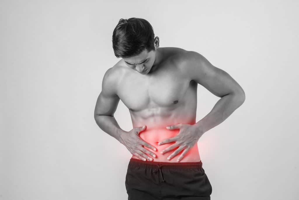 Young handsome Muscular man has gastritis pain
