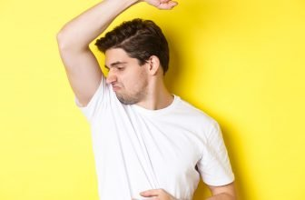 A man with yellow armpit skin smells smelling his underarms
