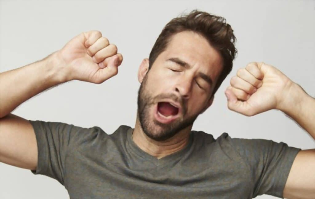 man yawning with two hand fisted